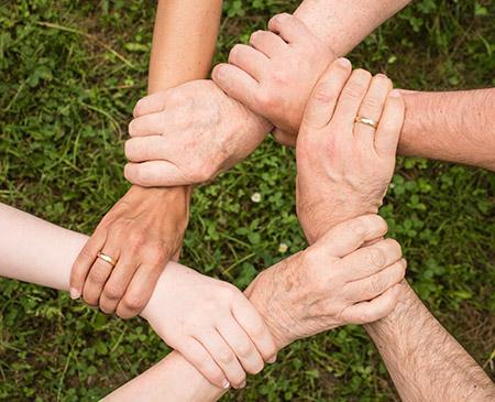 Image of six interlocked hands symbolizing team work.